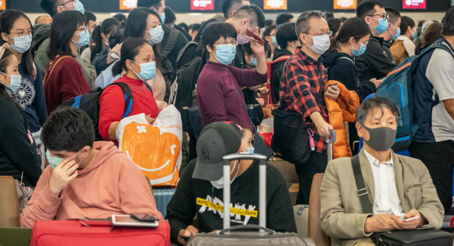 Travelers wearing face masks in Hong Kong because of Wuhan coronavirus infections. | Getty Images