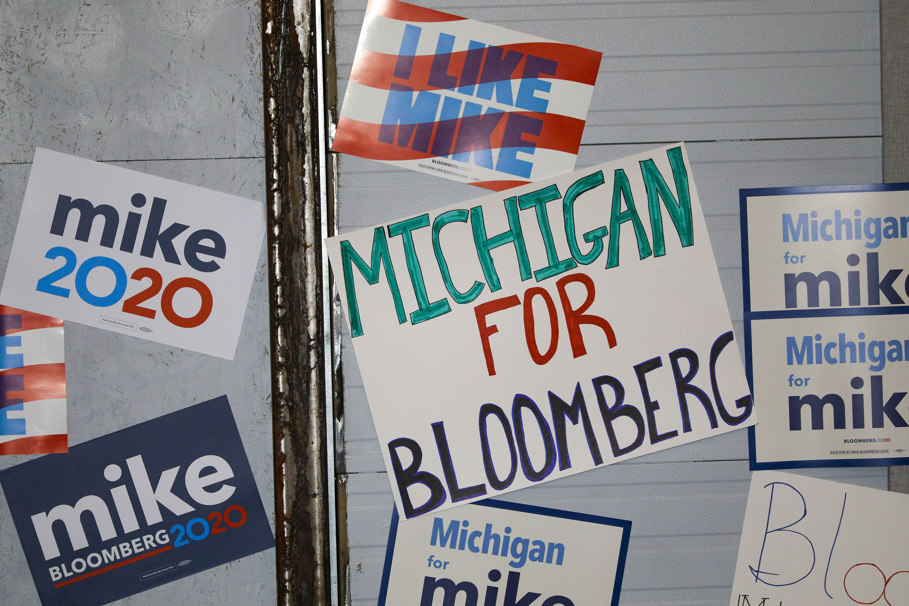 Signs are posted on a wall at a rally site where Democratic presidential candidate Mike Bloomberg held a campaign rally on Feb. 4