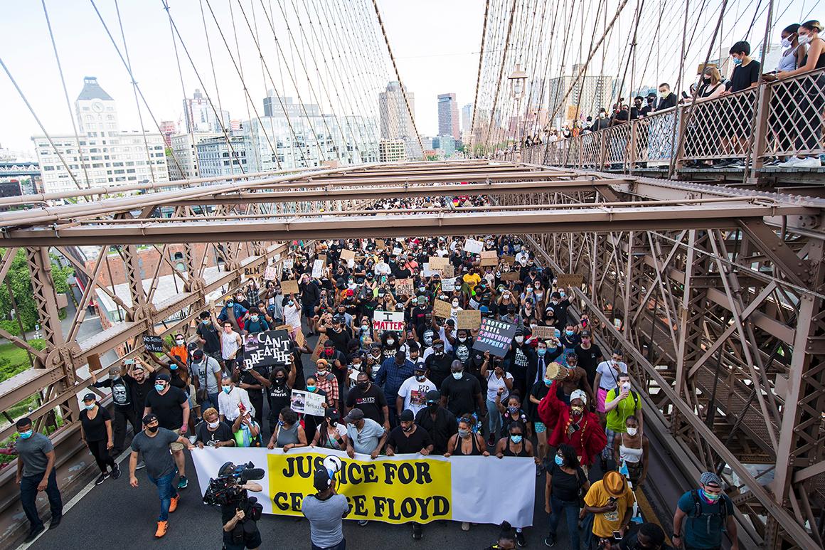 Activists walk across the Brooklyn Bridge