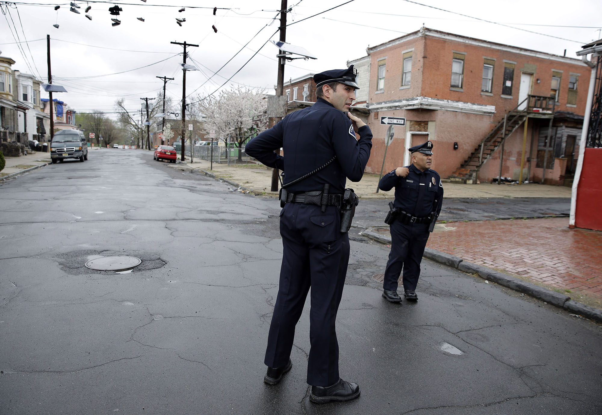 In this Tuesday, April 15, 2014 photograph, Camden County Metro police officers Lucas Murray, left, and Daniel Torres react to what they thought was a gunshot, as they patrol a neighborhood in Camden, N.J.